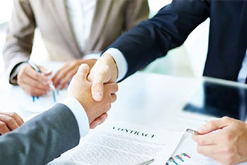 Two businessmen shaking hands over contract with other person signing in background