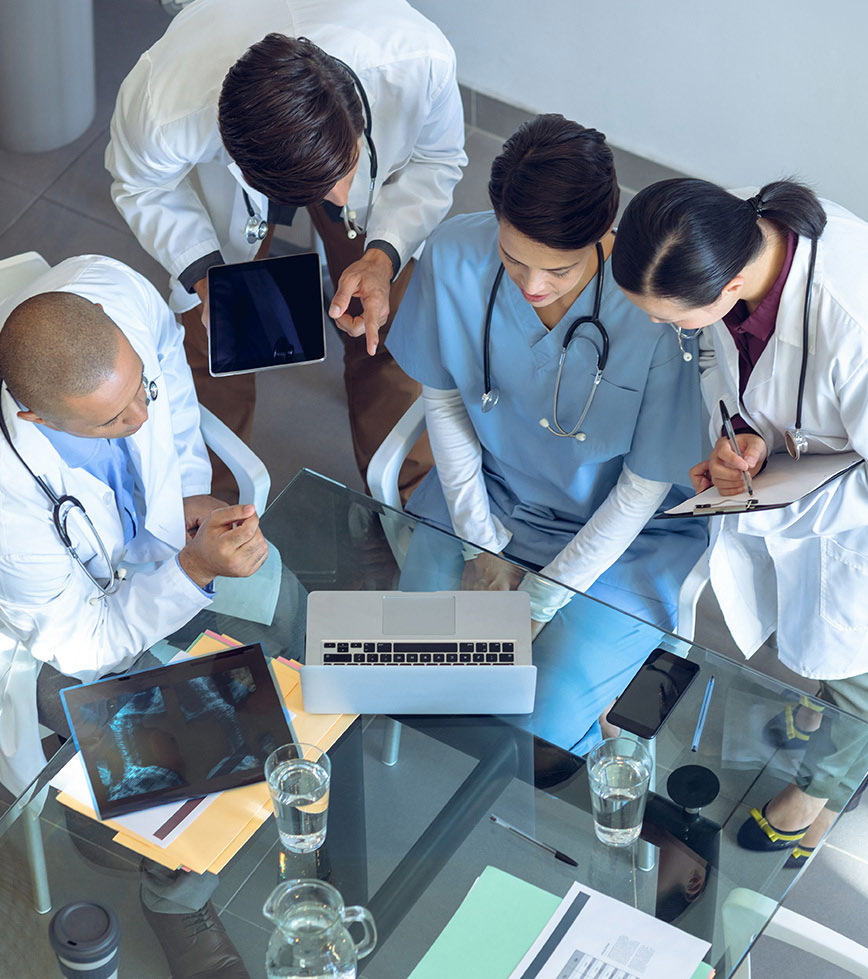 4 medical personnel looking at computer on glass table with water cups and x ray sheet on it