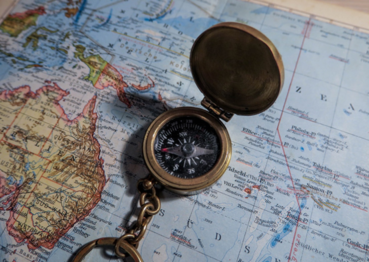round brass compass on world map