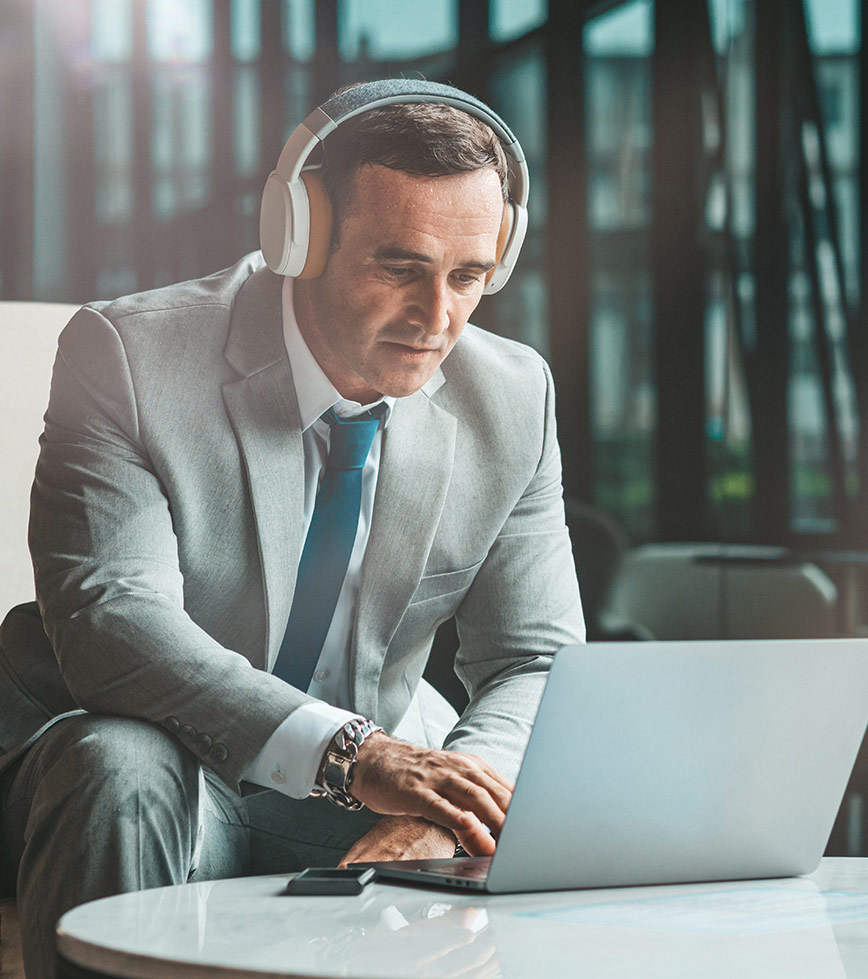 Man in grey suit with white over the head headphones on working on computer